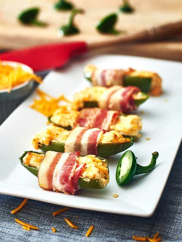Slightly crunchy jalapeños that are wrapped in bacon and filled to the brim with smooth cream cheese and melted cheddar cheese. www.showmetheyummy.com #jalapenos #spicy #jalapenopoppers #bacon #creamcheese #cheddarcheese #ranch #snacks #appetizers #baconwrappedjalapenopoppers #footballsnacks