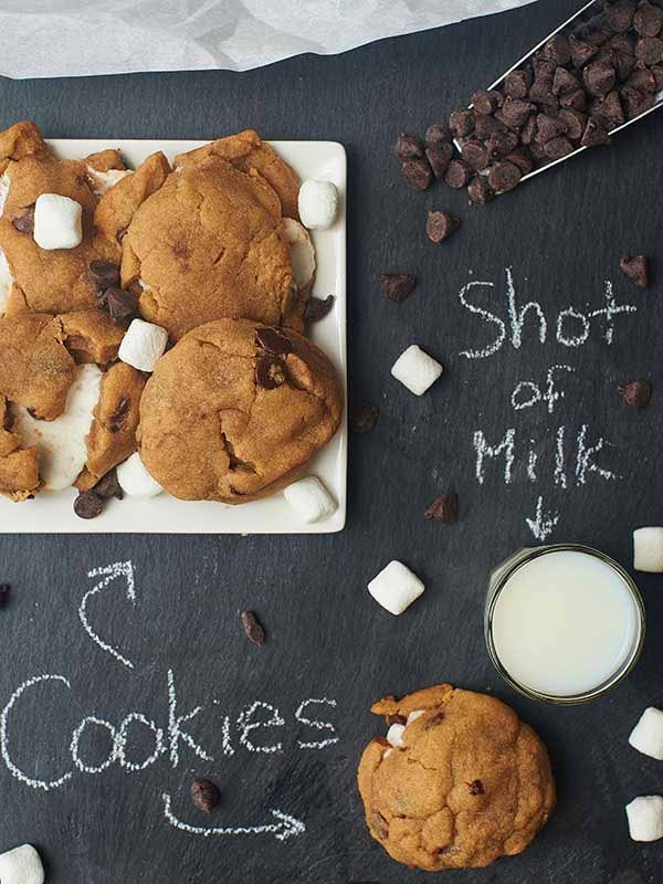 Marshmallow stuffed peanut butter chocolate chip cookies on plate next to glass of milk above