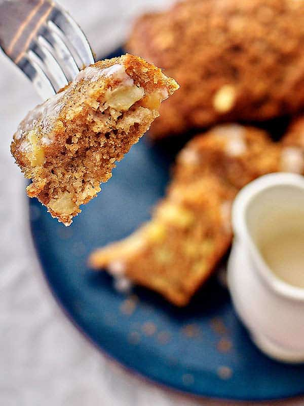 bite being picked up with fork of apple cake loaf above plate