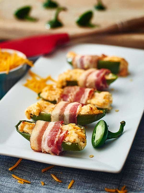 Slightly crunchy jalapeños that are wrapped in bacon and filled to the brim with smooth cream cheese and melted cheddar cheese. www.showmetheyummy.com #jalapenos #spicy #jalapenopoppers #bacon #creamcheese #cheddarcheese #ranch #snacks #appetizers #baconwrappedjalapenopoppers #footballsnacks #baked