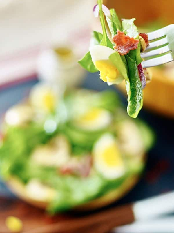 forkful of warm bacon spinach salad