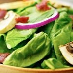 Crispy bacon, hard boiled egg, crunchy red onion, meaty mushrooms, and tender spinach. All smothered in a warm creamy bacon dressing. This warm bacon spinach salad is a must on a cold, fall day! #salad #healthy #bacon #bacondressing #mushrooms #redonion www.showmetheyummy.com