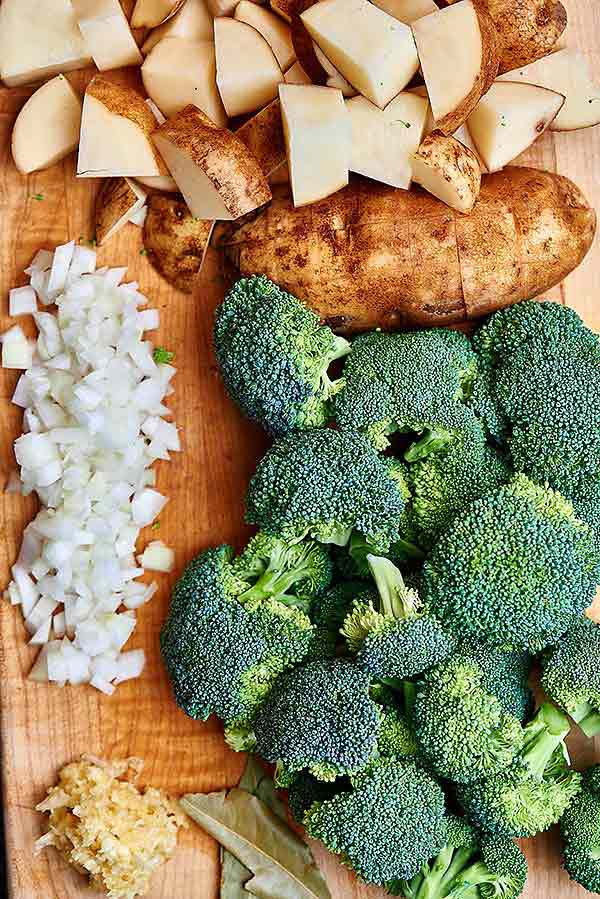 Potatoes, broccoli, onion, garlic, and bay leaves on cutting board above