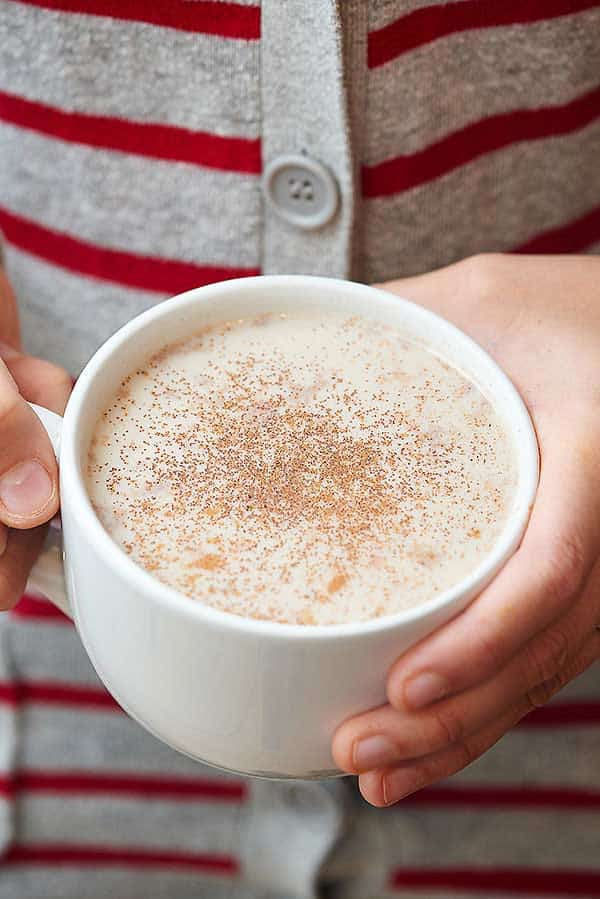 Chai latte in mug held in two hands