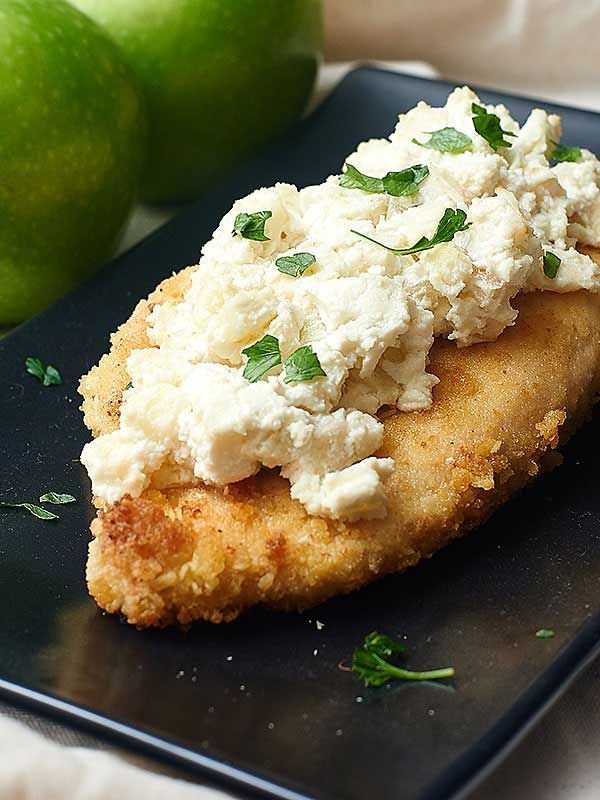 Goat Cheese Apple Chicken. Yum. Hot and juicy on the inside, slightly crunchy exterior, perfectly salty, and topped with the perfectly sweet, tart, and tangy apple and goat cheese. https://showmetheyummy.com #chicken #goatcheese #apple #breading