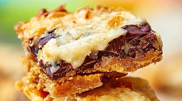 These ugly duckling bars may not be much to look at, but they sure taste good! Start with a graham cracker crust and pile on gooey chocolate chips, sweet coconut flakes, and sweetened condensed milk! www.showmetheyummy.com #bars #dessert #chocolatechips #coconut #sweetenedcondensedmilk