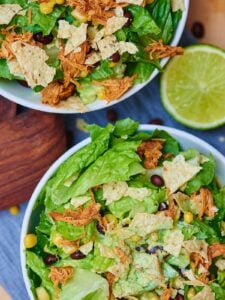 This BBQ chicken salad starts with a base of romaine, is topped with lightly salted corn and black beans, shredded chicken that's been cooking all day in the crockpot, a few crushed tortilla chips, and a Ranch yogurt dressing! Healthy, filling, and delicious! showmetheyummy.com #healthy #salad #bbq #crockpot #chicken