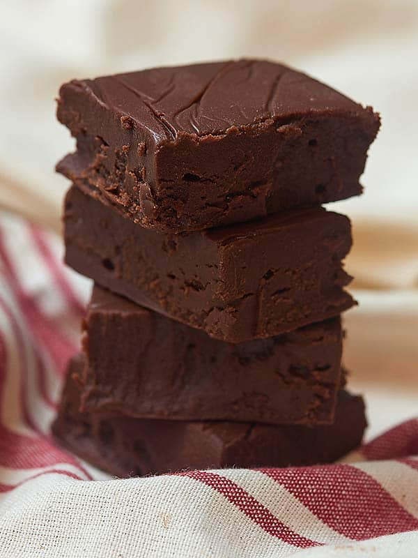 This easy chocolate fudge is ultra thick, smooth, creamy, and extra chocolatey. Not only does it require just a singular bowl, it also has a simple ingredient list (only 5!), and is made in the microwave! I promise, it'll totally be worth that 90 seconds it takes you to make it! showmetheyummy.com #fudge #chocolatefudge #easychocolatefudge #microwave #holidaytreats