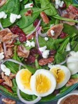A maple bacon salad. Need I say more? Spinach is topped with goat cheese, bacon, and candied pecans, and then smothered in a yummy maple bacon dressing! This salad is nutritious, delicious, and can be customized to suit your taste bud needs. showmetheyummy.com #maplebacon #salad #bacon #bacondressing #goatcheese
