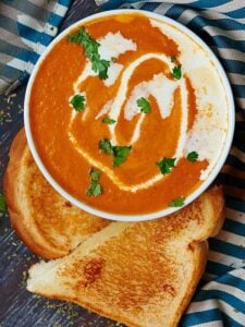 So long canned soup! This roasted tomato soup, is so good and fast to put together. I love how roasting the tomato, onions, and garlic brings out sooo much flavor. The tomato flavor is subtle and bright, and it's so creamy and thick without needing much butter at all! Can we vegetarian and vegan friendly! showmetheyummy.com #soup #roastedvegetables #tomato #meatless #vegetarian #vegan #roastedtomatosoup