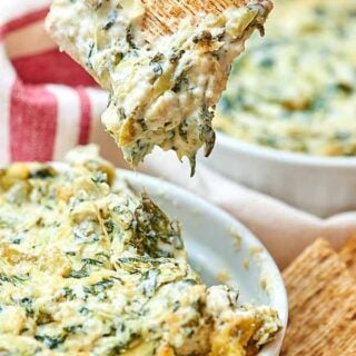 This spicy spinach artichoke dip is hot, creamy, spicy, overall full of flavor, and you get some veggies in, too! Don't be alarmed if you see someone licking the bottom of the bowl...that's totally normal...at least in our house. ;) showmetheyummy.com #appetizer #vegetarian #holiday #dips