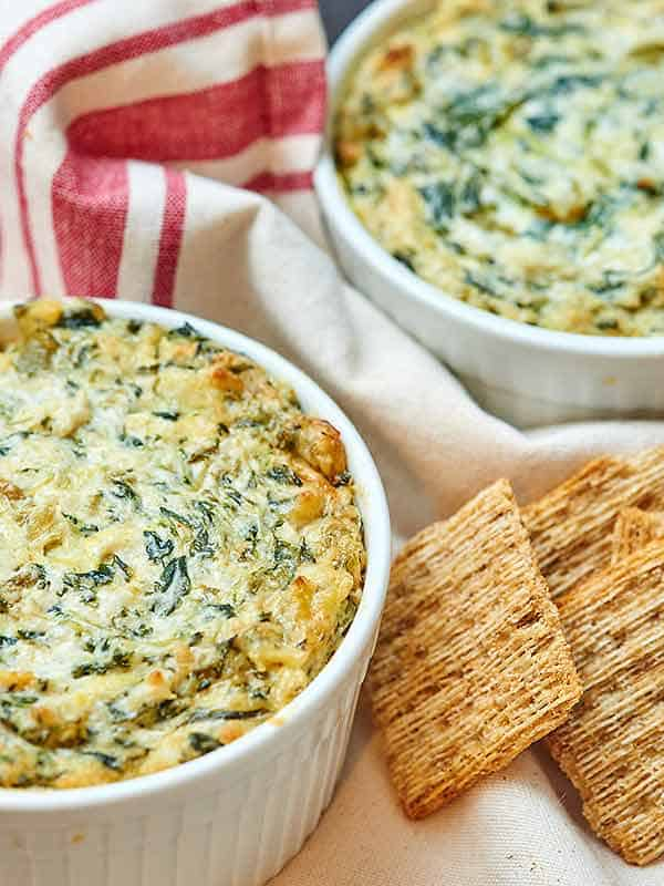 two bowls of spinach artichoke dip next to crackers