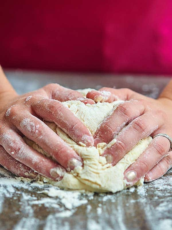 Pizza dough being kneaded with hands