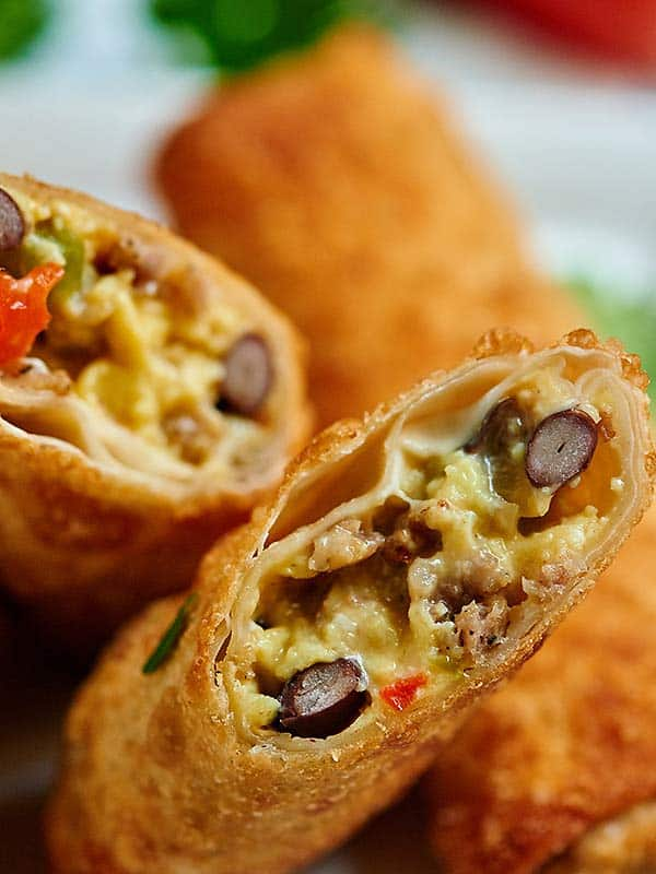 These breakfast egg rolls can be a fun change to your breakfast routine! The outside is perfectly crunchy and is filled with creamy eggs, gooey cheese, slightly crunchy veggies, salty sausage, and yummy black beans! It's hearty, it's delicious, and you're going to be hooked after one bite! showmetheyummy.com #eggrolls #breakfast #eggs #vegetables #sausage #fried