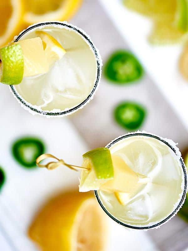 A jalapeño margarita with homemade jalapeño infused tequila! These margaritas aren't like the drinks you get in a restaurant...the ones that are 16 oz, have a splash of tequila, and the rest is filled with half watered down ice, and super sugary margarita mix that makes your teeth hurt. These jalapeno margaritas are strong, have no added sugar, and really pack a punch! showmetheyummy.com #tgif #cocktails #jalapeno #margarita #happyhour #drinks
