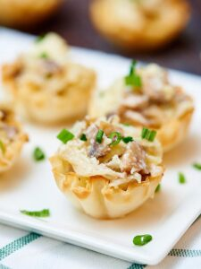 If you're looking for bite sized appetizers to serve a crowd, or just for a nice dinner at home for two, look no further because these mini caramelized onion, mushroom, and apple tarts are just a little sweet, a lot of savory, and have an amazing texture! Crunchy from the shell, and creamy and soft from the filling. The perfect bite if you ask me! showmetheyummy.com #appetizer #vegetarian #tart #appletart #oniontart #superbowl