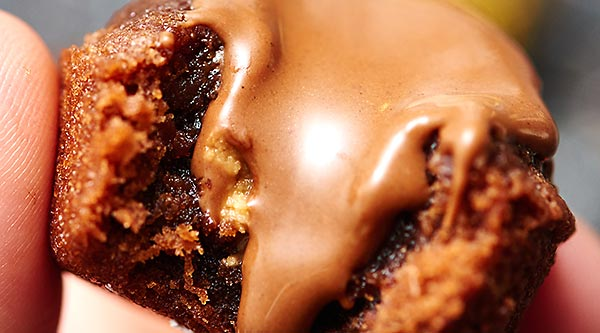 These peanut butter cup stuffed brownie bites are oogey gooey at it's finest! While these brownie bites would be great without the peanut butter cups, because they're so moist and fudgy, the Reese's really takes it to the next level! Biting into a rich, chewy brownie, and a melty peanut butter cup is pure heaven. showmetheyummy.com #brownies #dessert #browniebites #peanutbuttercup #reeses #stuffedbrownies #candy