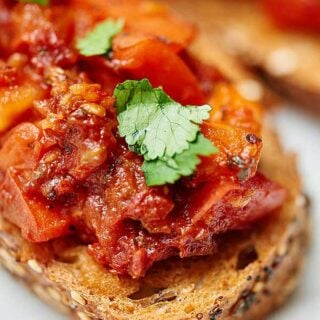This sun dried and roma tomato bruschetta is truly flavorful and has amazing texture...I swear you won't believe it's healthy for you! I love the toasty crunch of the bread that's piled with two types of warm, juicy, tender tomatoes, spicy garlic, tangy balsamic, and sweet basil! showmetheyummy.com #bruschetta #tomato #healthy #vegan #vegetarian