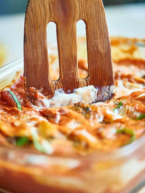 wooden spatula being dipped into baking dish of spinach stuffed shells