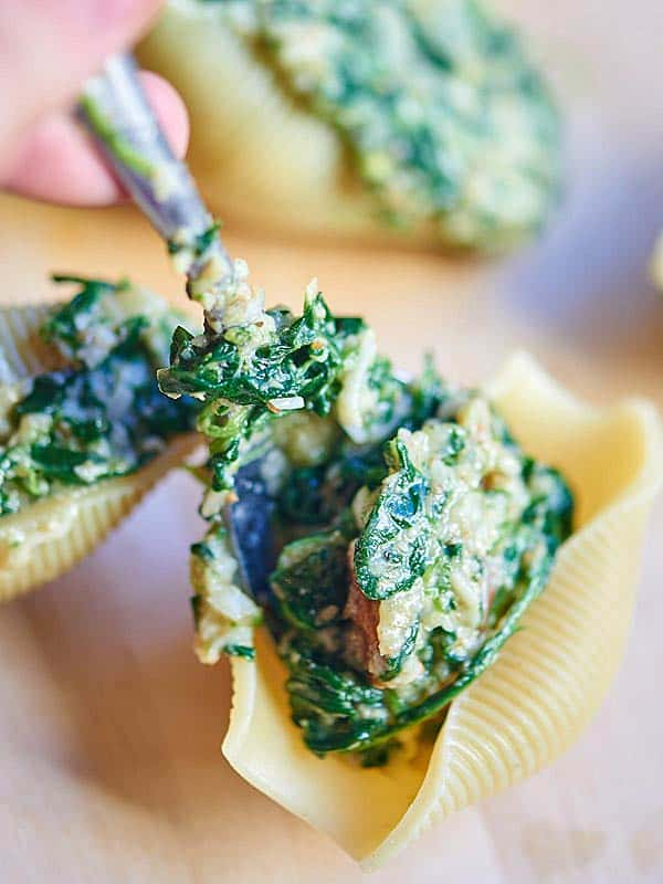 These cheesy spinach stuffed shells are truly unique! I love the health benefits of adding wheat germ and it really doesn't effect the flavor, if you ask me. I also love that it's packed with spinach. Then to offset all the health benefits, you really can't go wrong with cheese and alfredo sauce. ;) The pecans add a really pleasant and unexpected crunch to give the dish a little texture! showmetheyummy.com #stuffedshells #vegetarian #pasta #carbs #cheese