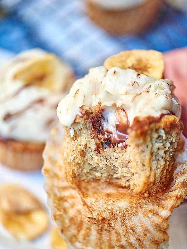 These are chocolate hazelnut banana cupcakes with marshmallow frosting. A simple banana cupcake is stuffed with Nocciolata, and smothered in a toasted marshmallow buttercream. I love how moist and fluffy the banana cupcakes are, the chocolate hazelnut spread is just....awesome, and that toasted marshmallow frosting? It's sweet, it's thick, it's creamy, and I love the texture from the toasted and chewy marshmallow bits. showmetheyummy.com #banana #chocolate #hazelnut #marshmallow #cupcakes #dessert