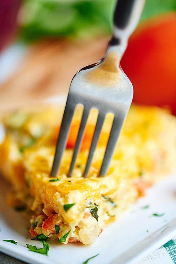 Slice of quiche being stabbed with fork
