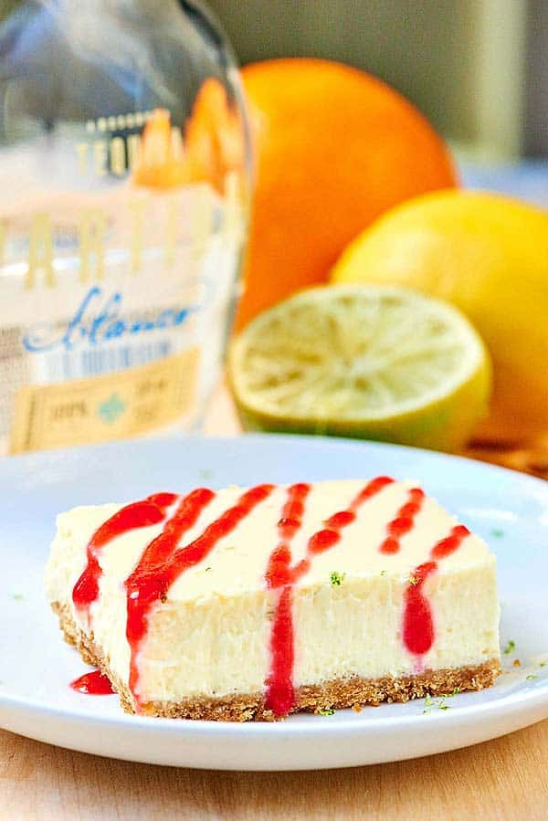 These tequila lime cheesecake bars are perfect for celebrating National Margarita Day! The slightly crunchy pretzel crust mimics the salty rim on a margarita and the cheesecake filling is so creamy and filled with cream cheese, lime juice, tequila, and grand mariner! It's like eating your favorite margarita in bar form! ;) showmetheyummy.com #tequila #grandmariner #margarita #cheesecake #bars #pretzels #lime