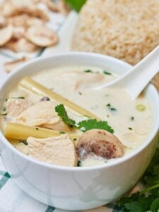 This Tom Kha Gai soup may not be 100% authentic, but I'd take this over take out any day! It's really easy to put together and it's a whole heckofalot cheaper than paying someone else to make it for you! This soup is a little limey, so creamy of the coconut milk, has a nice back heat from the cayenne, and is full of tender chicken! showmetheyummy.com #tomkhagai #soup #coconut #chicken #coconutchickensoup #spicy #thai #ethnic