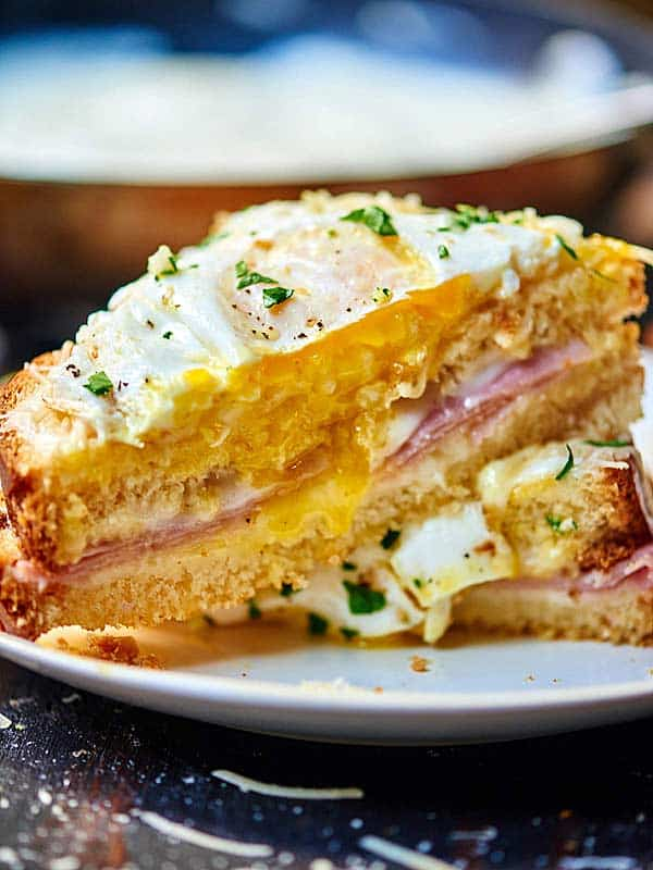 Croque Madame sandwich cut in half, one half resting on the other