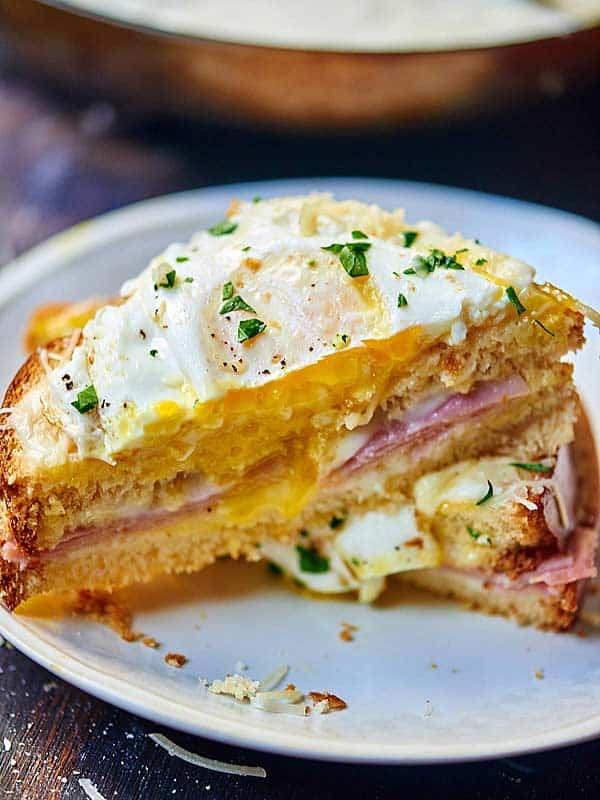 A croque madame: a classic french sandwich made with sweet brioche, salty ham, sharp gruyere and topped with a bechamel sauce, more cheese, and a fried egg! showmetheyummy.com #french #sandwich #breakfast #lunch #eggs #bechamel #cheese #ham