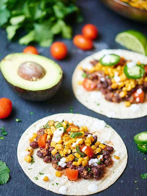Two black bean and corn tacos next to half avocado