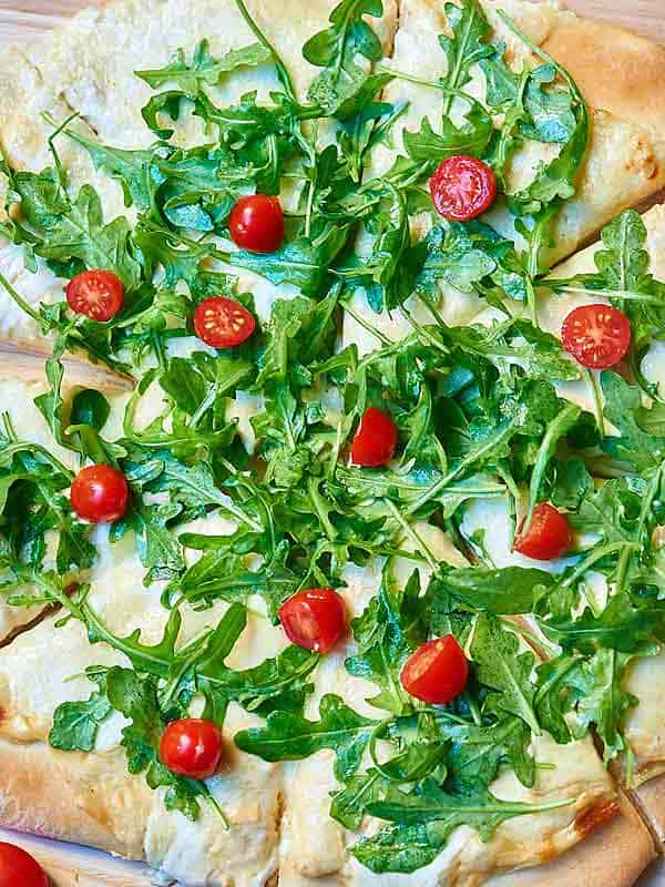 roasted garlic white cheese pizza with arugula above