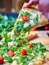 Once you've tasted this roasted garlic white cheese pizza with arugula salad you'll never go back to store bought pizza again! Homemade crust is topped with a creamy, slightly spicy roasted garlic sauce, two types of cheese, and is baked to ooey gooey perfection! It's then topped with a fresh arugula salad! Can we say perfection?! showmetheyummy.com #pizza #arugula #whitepizzasauce #whitepizza #cheese #vegetarian #garlic