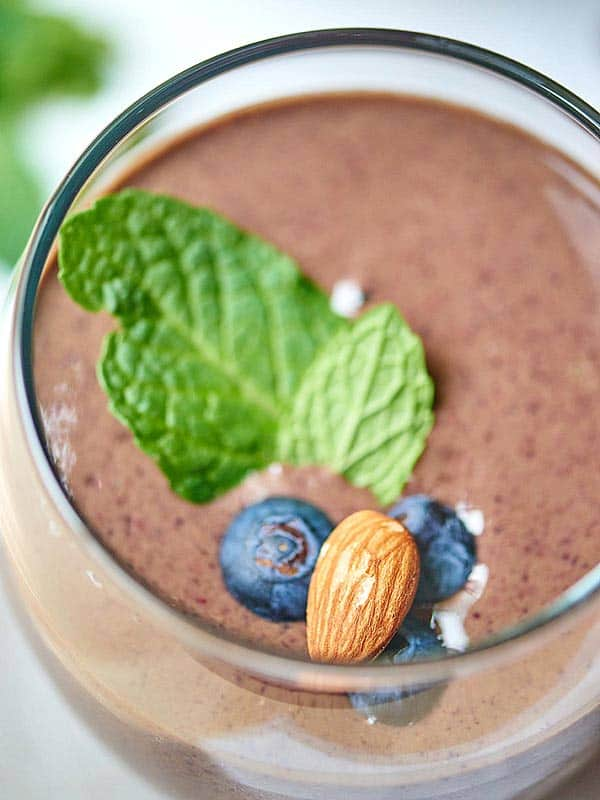 Chocolate berry green protein smoothie in cup with garnishes above