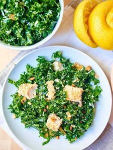 Kale Salad with Baked Almond Chicken. A healthy, protein packed salad full of massaged kale, pecorino romano cheese, golden raisins, almond chicken, and smothered in a fresh, lemony dressing! showmetheyummy.com #kale #salad #healthy #chicken #protein #lemon