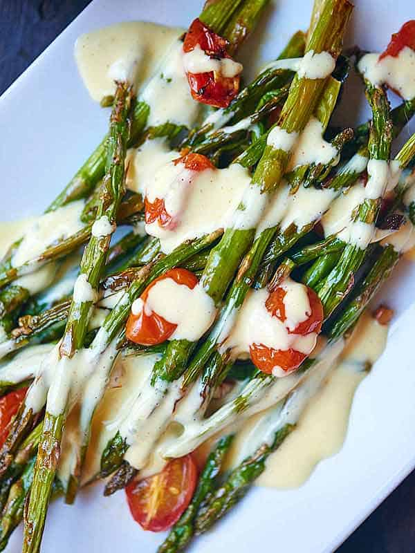 roasted asparagus and tomato with lemon garlic hollandaise on plate above