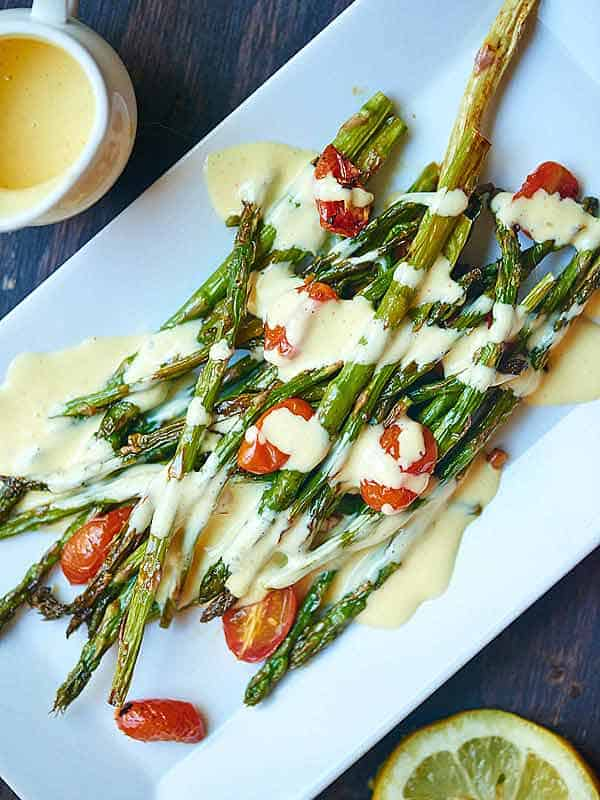 roasted asparagus and tomato with hollandaise sauce on plate above