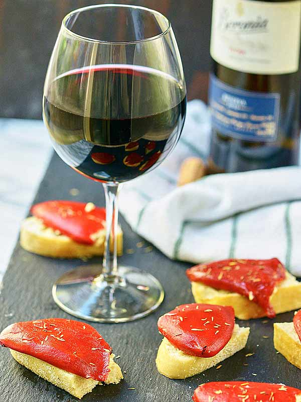 Goat Cheese Stuffed Piquillo Peppers are the perfect tapas! Mild piquillo peppers are stuffed with a goat cheese and manchego filling and paired with a Spanish red wine. showmetheyummy.com #spanish #winepairing #appetizer #vegetarian #goatcheese #tapas #redwine #piquillopeppers