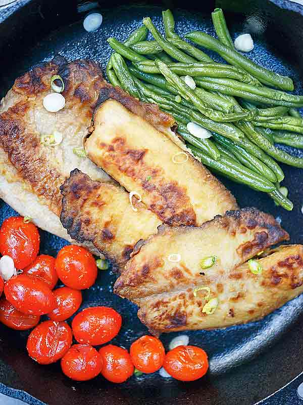 Garlic tilapia in skillet with veggies above