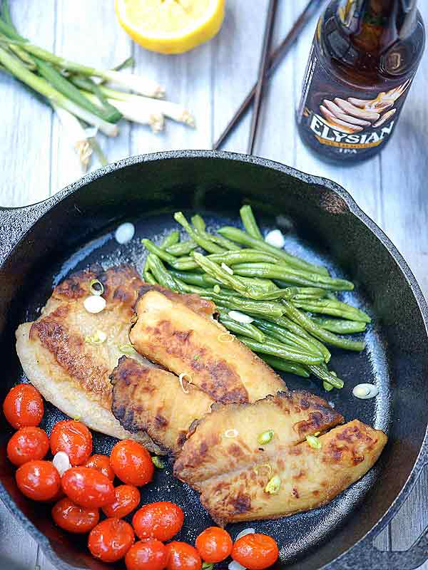 Garlic tilapia in skillet with cherry tomatoes and green beans above