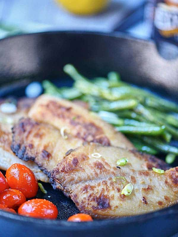 Tilapia with veggies in skillet