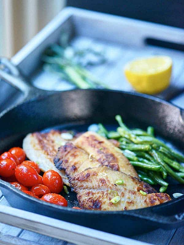 Honey, soy, and garlic tilapia in skillet from side