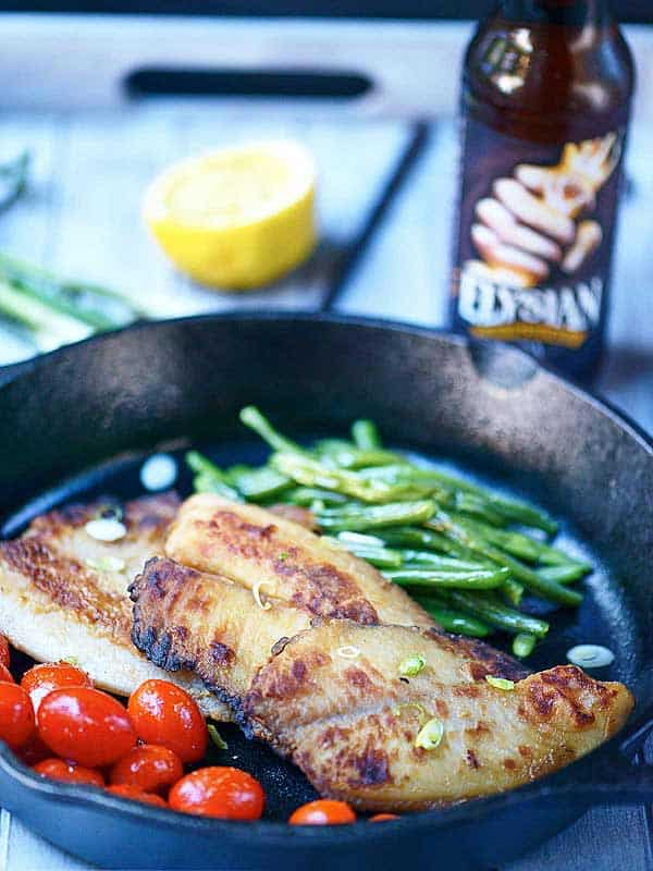 Honey, soy, and garlic tilapia in skillet with tomatoes and green beans