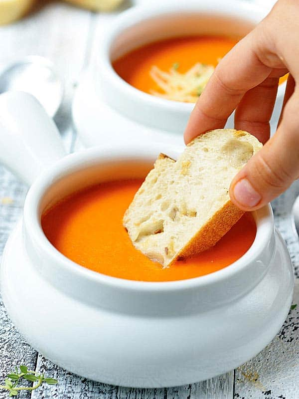 bread dipped in bowl of soup