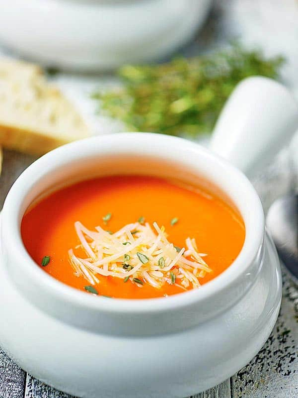 bowl of roasted red pepper soup with parmesan cheese