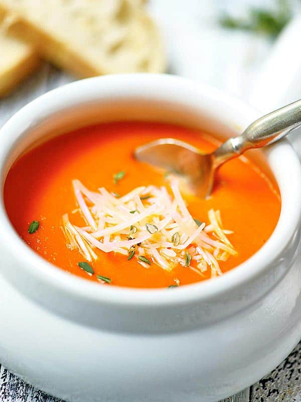 bowl of roasted red pepper soup with spoon and parmesan cheese