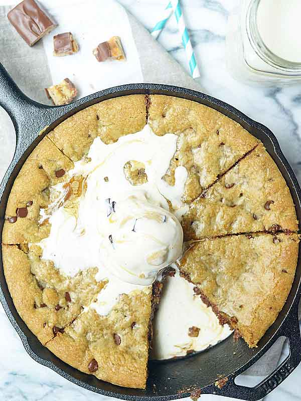 snickers stuffed deep dish chocolate chip cookie in skillet with ice cream