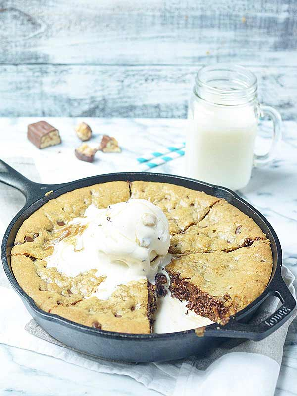 skillet with snickers stuffed deep dish chocolate chip cookie, glass of milk in background