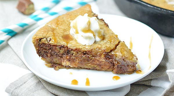 Snickers Stuffed Deep Dish Chocolate Chip Cookie. Made in a skillet, this cookie is thick, gooey, and has that great sweet/salty combo! Top it with cookie dough ice cream to take this dessert over the top! showmetheyummy.com #deepdish #cookie #snickers #candy #skillet #dessert #chocolate #icecream