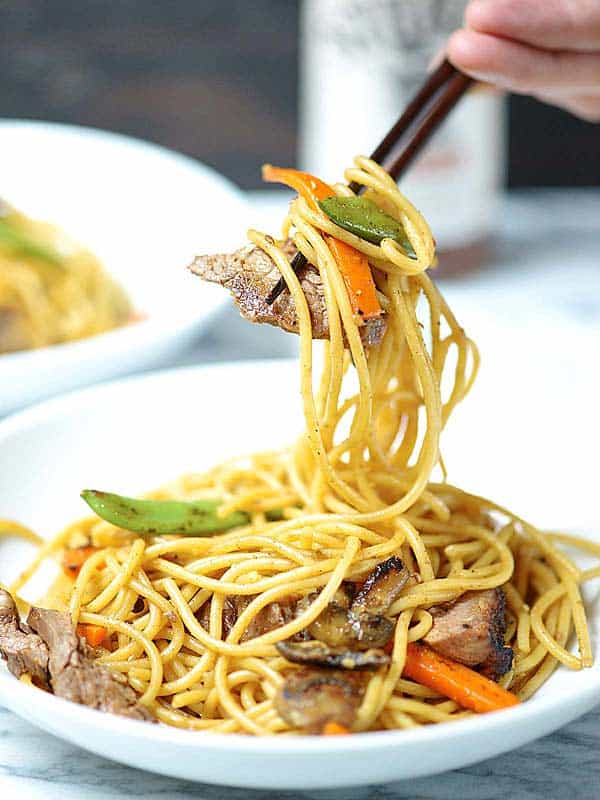 beef lo mein being picked up with chopsticks